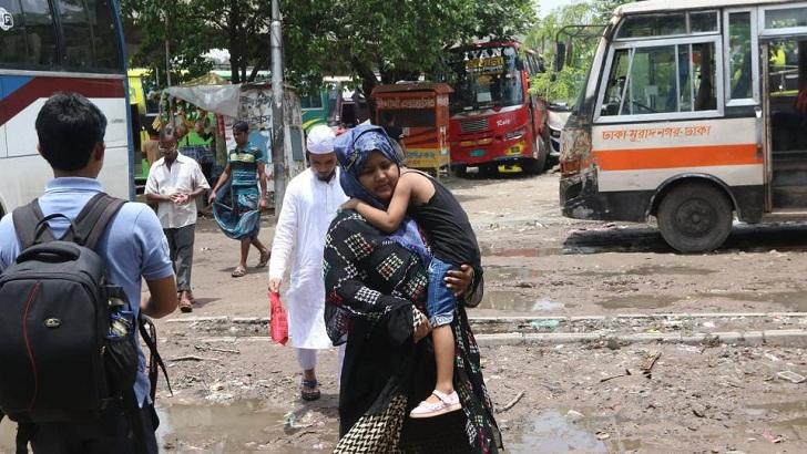 রাজধানীতে ঘুমন্ত শিশুকে কোলে নিয়ে বাসের অপেক্ষায় এক নারী