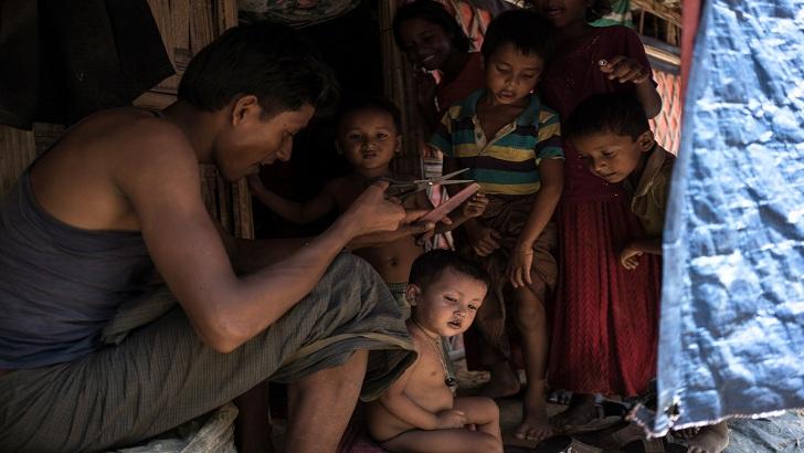 বালুখালী ক্যাম্পে নিজের ছোট ছোট সন্তানদের চুল কেটে দিচ্ছেন এক রোহিঙ্গা-আল জাজিরা