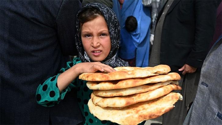 আফগানিস্তানের রাজধানী কাবুলে খাবার হাতে এক কিশোরী। ছবি: স্কাই নিউজ