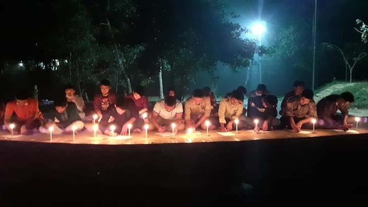 মোমবাতি প্রজ্বালন করে প্রতীকী পরীক্ষা দিল কুবি শিক্ষার্থীরা